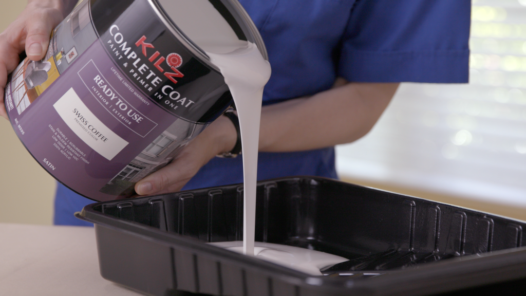 Person pouring Kilz Complete Coat Paint and Primer in One into a paint tray