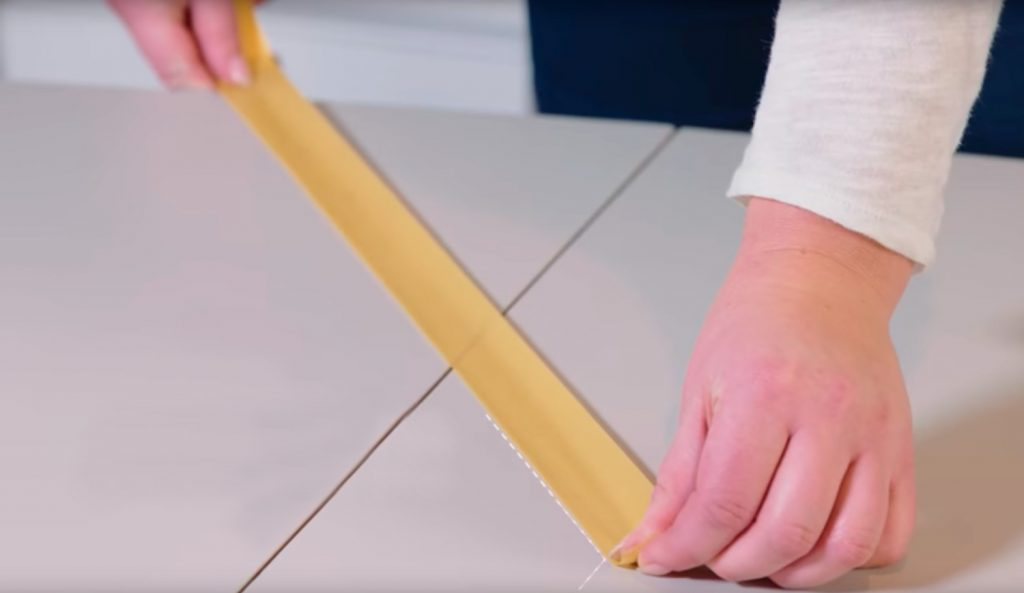 Person taping a table to paint it