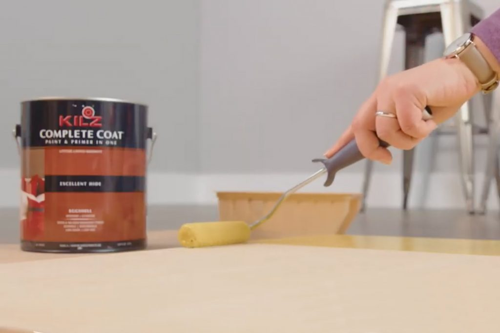 Person putting Kilz Complete Coat Paint and Primer in one on a table