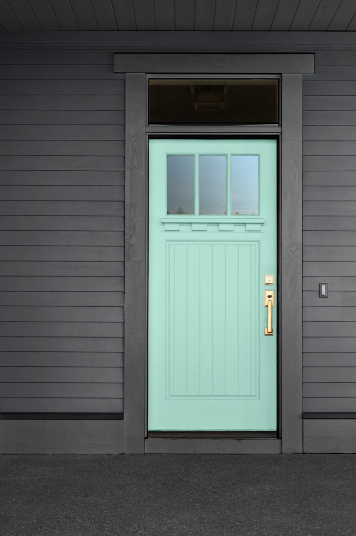 Front door painted mint green surrounded by black trim and black siding