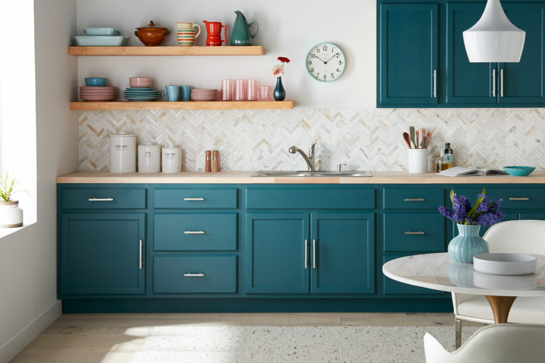 White kitchen with dark teal cabinets and a cream and white colored back splash
