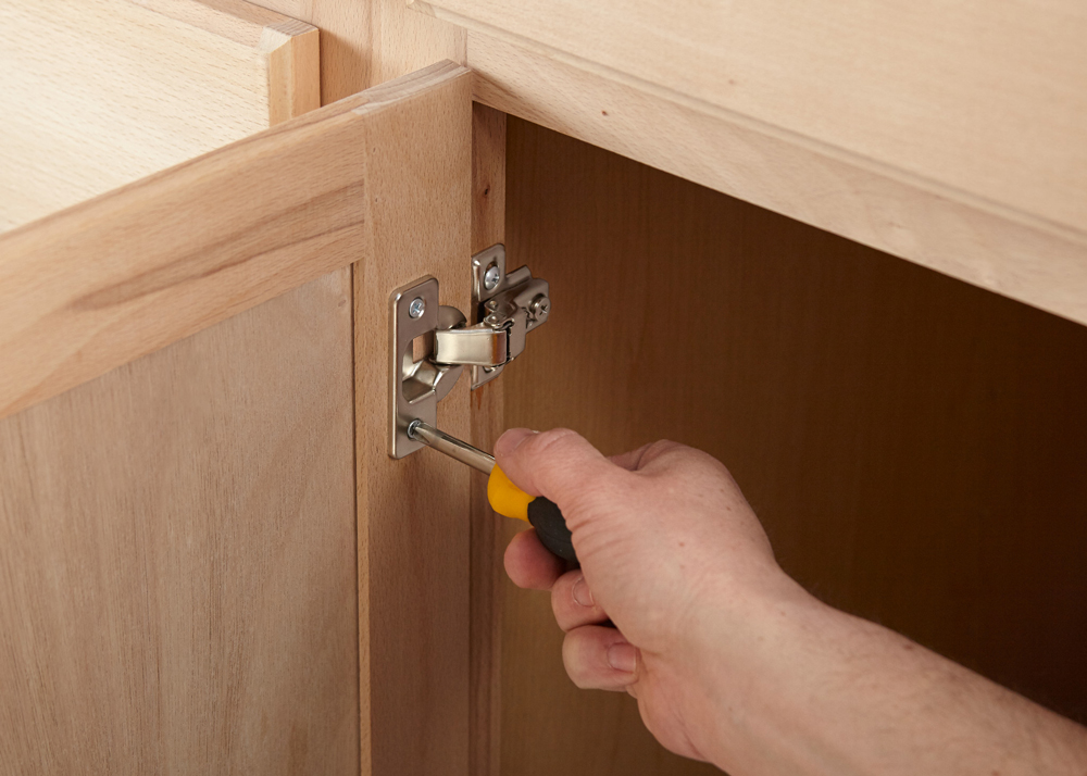 Person screwing in a hinge on a cabinet