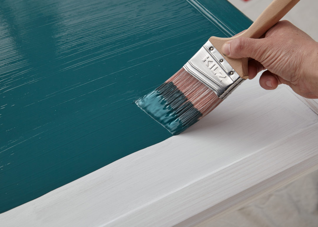 Person painting a white cabinet the color teal with a Kilz paintbrush