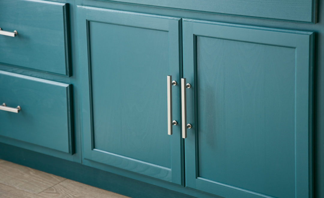 Teal colored cabinets with silver handles