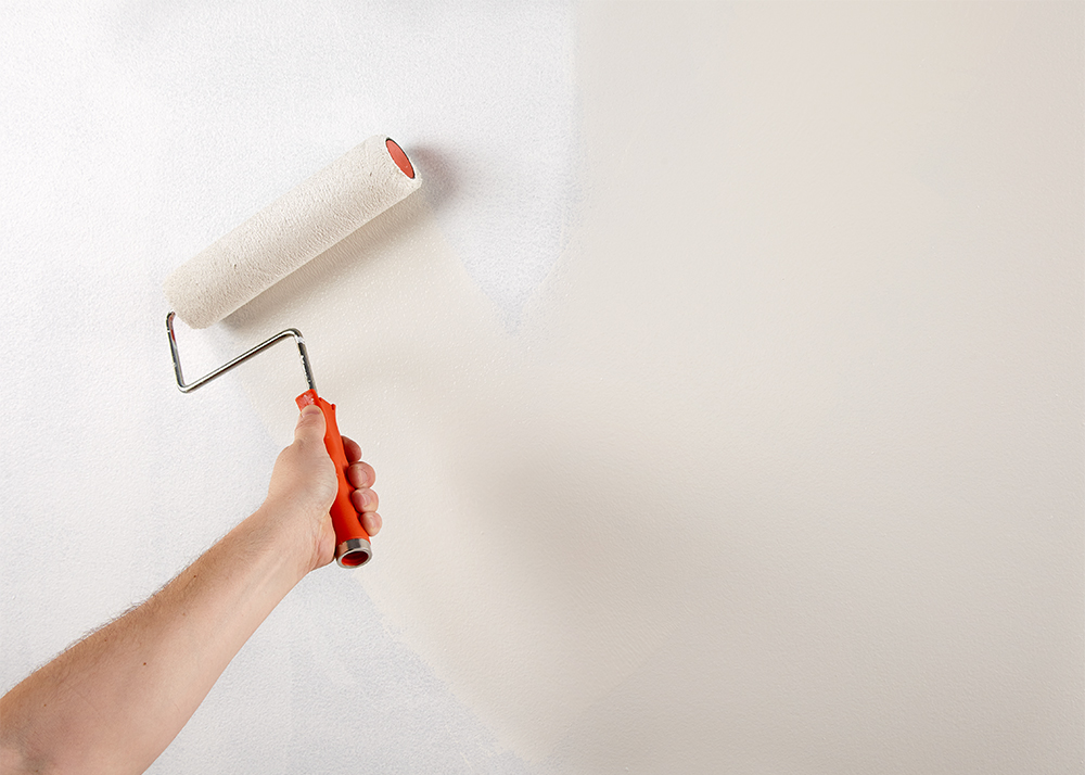 Person painting a wall the color cream