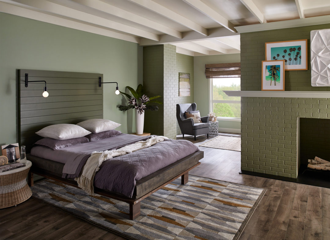Bedroom with green walls and a green fireplace with a bed that has purple sheets and pillows
