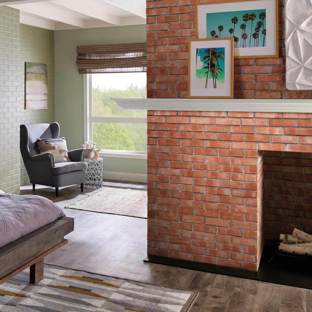 Bedroom with a red brick fireplace and a sitting area with a window