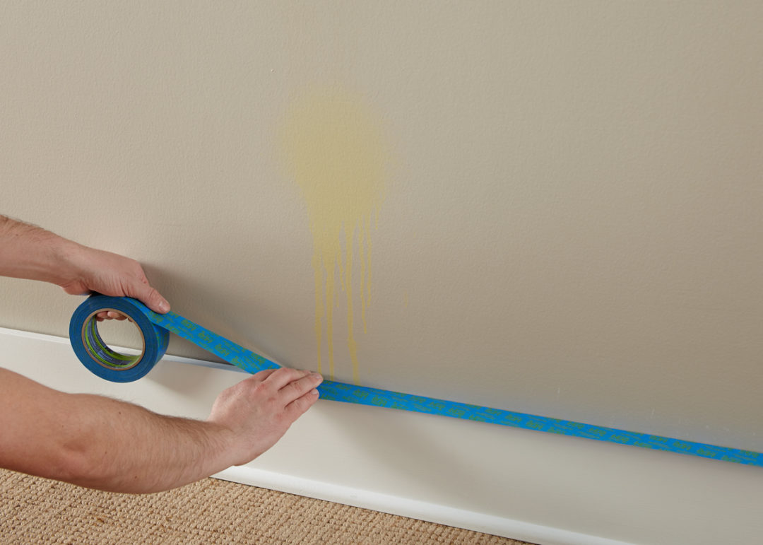 Person taping the baseboard of a wall with a stain on it