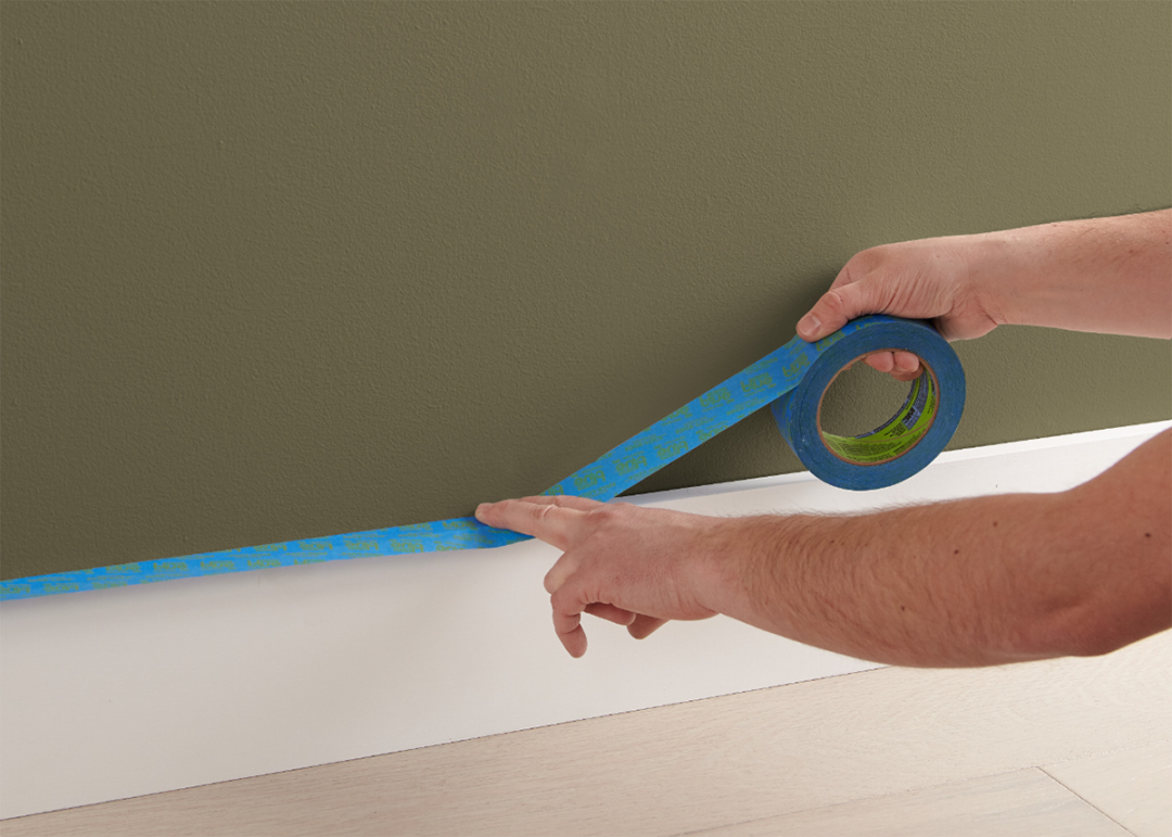 Person taping the baseboard of a green wall