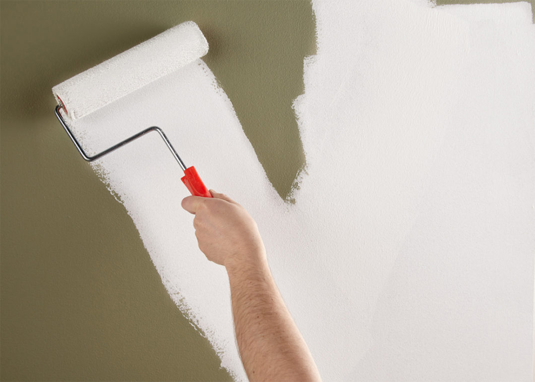 Person painting white over a green colored wall