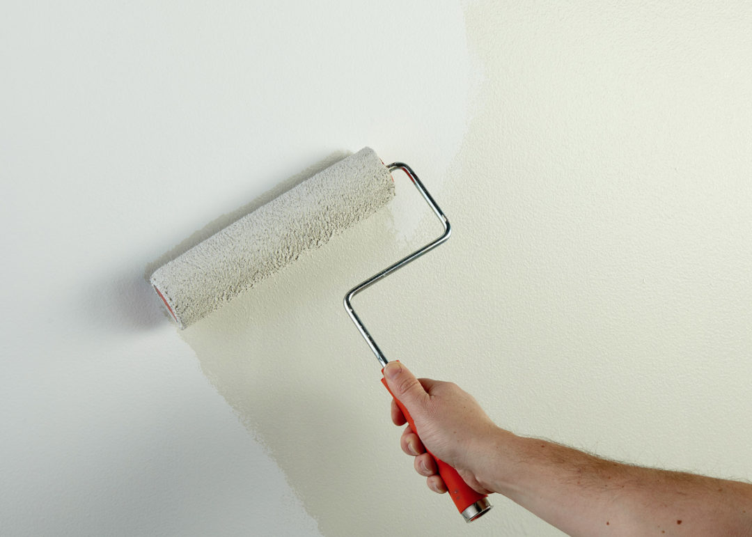 Person painting a wall cream