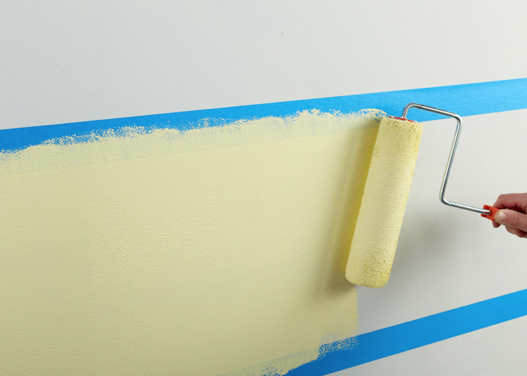 Person painting a portion of a wall yellow