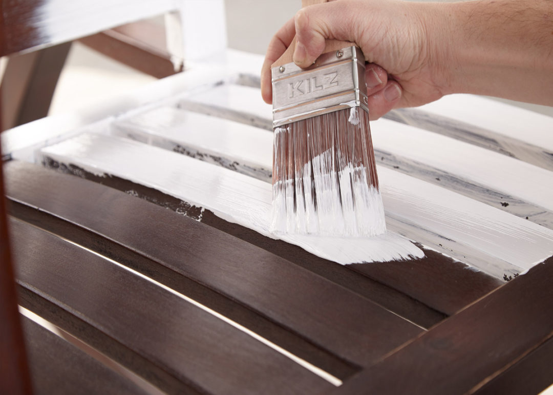 Person painting wood planks white