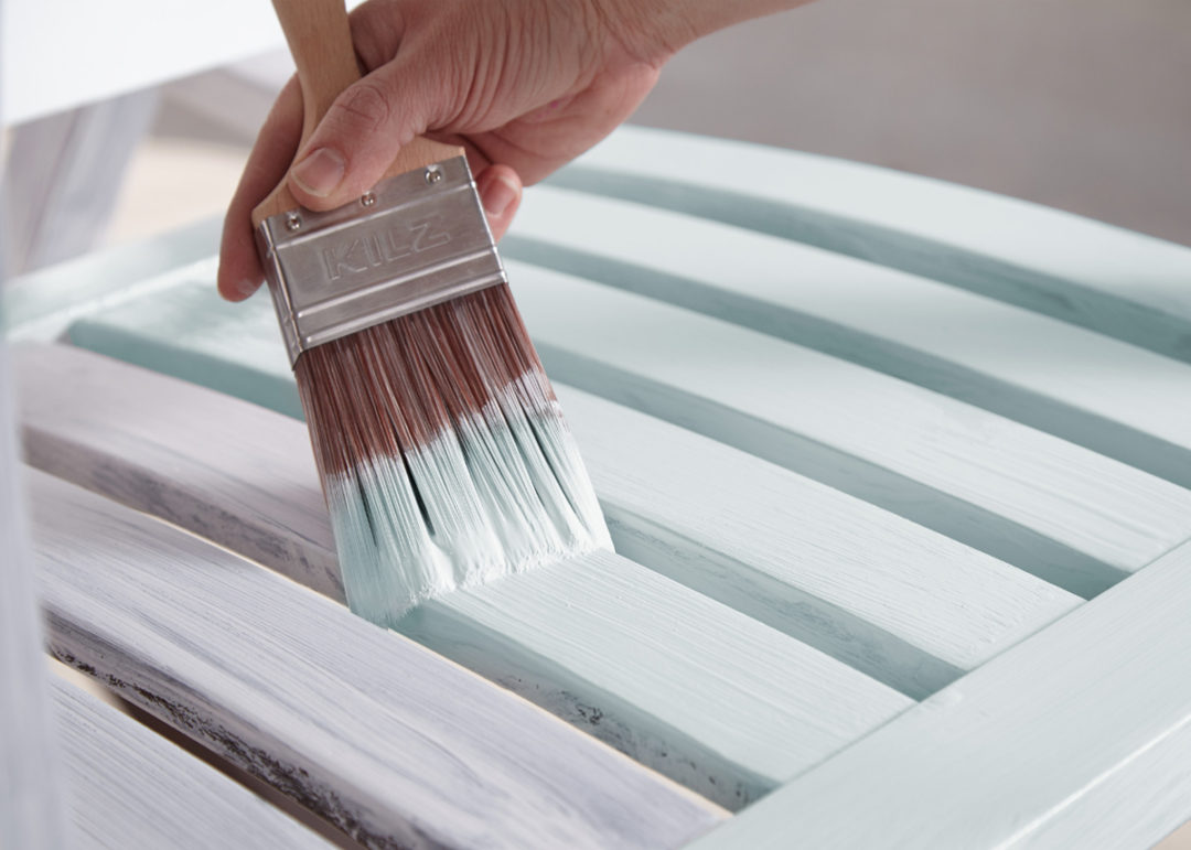 Person painting wood planks light blue