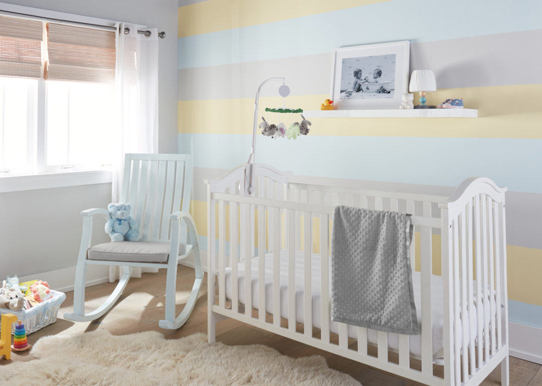 Nursery with yellow, grey, and blue walls with a white crib