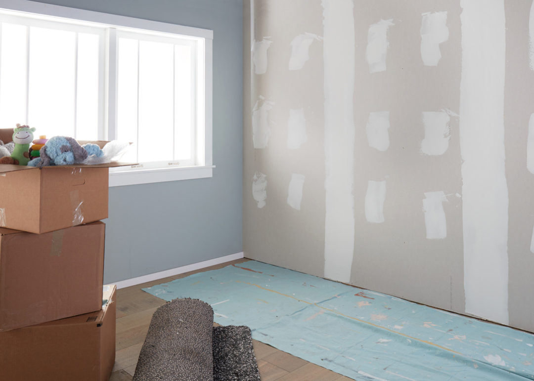 Room with one blue painted wall and another wall in the middle of a paint color change