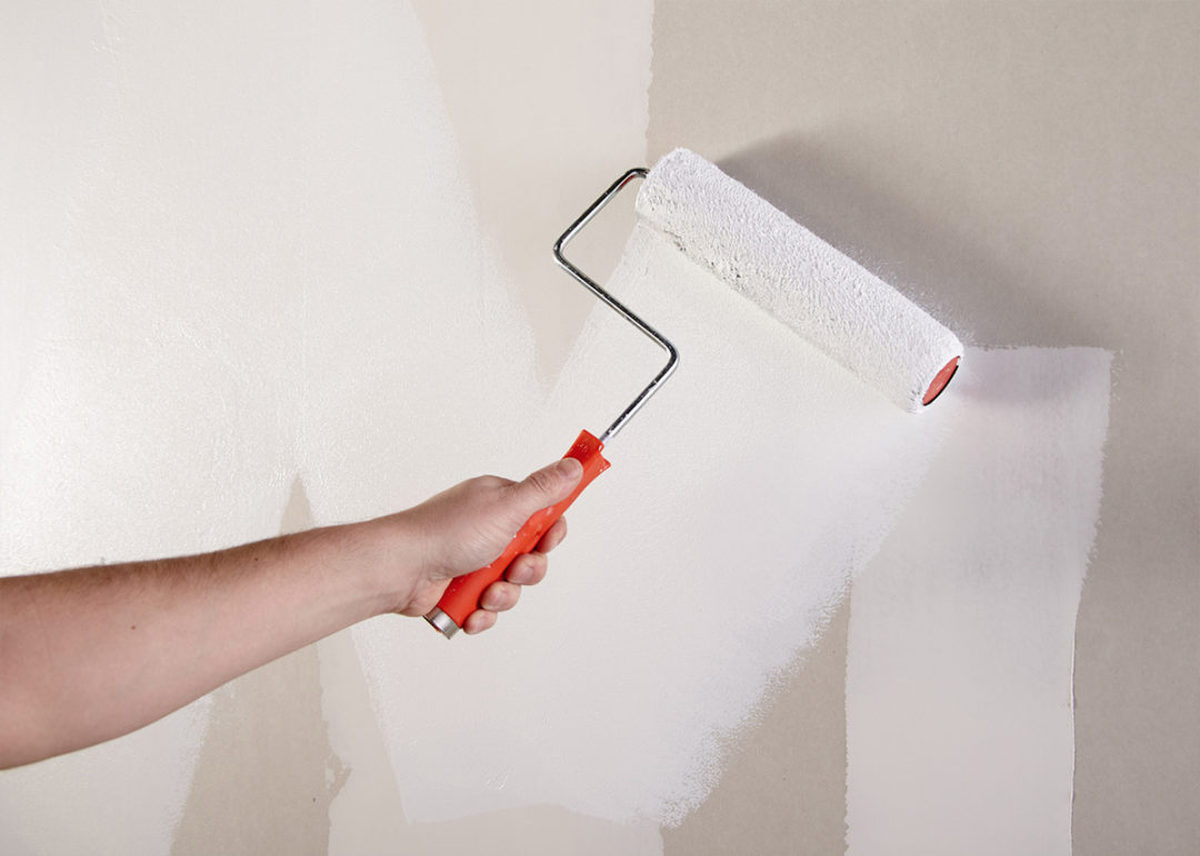 Person painting a wall white