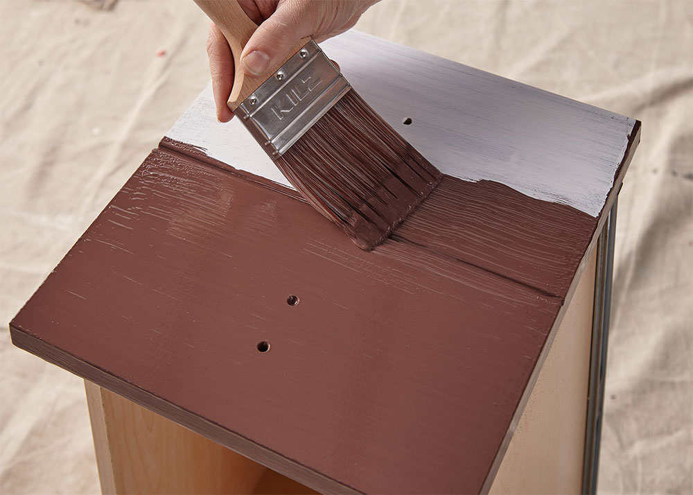 Person painting a desk drawer maroon