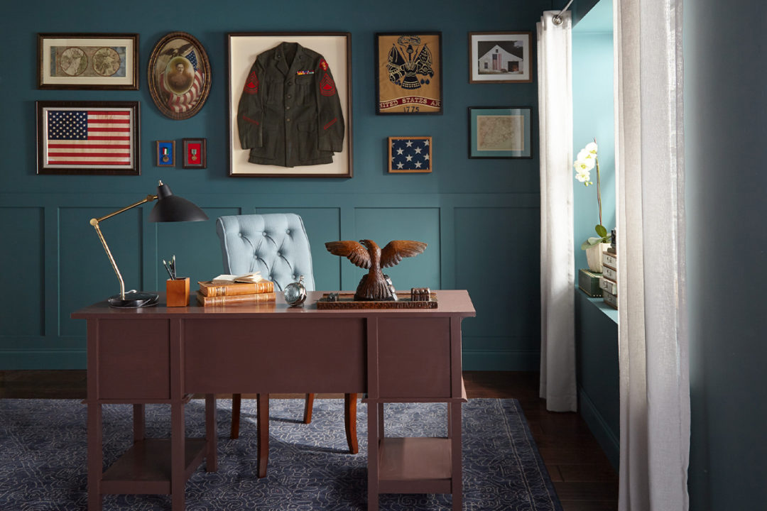 Office with blue walls and military decor on the walls and on the desk