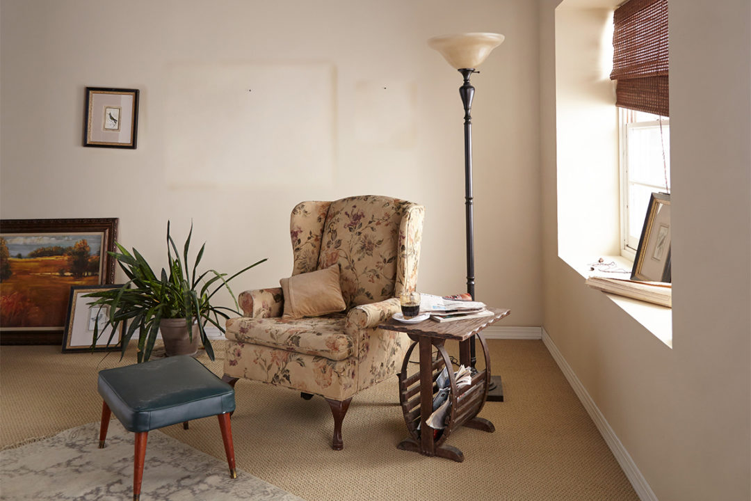 Office with cream colored walls and a floral chair