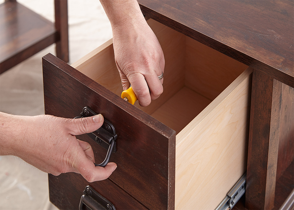Person screwing off the handle to a drawer
