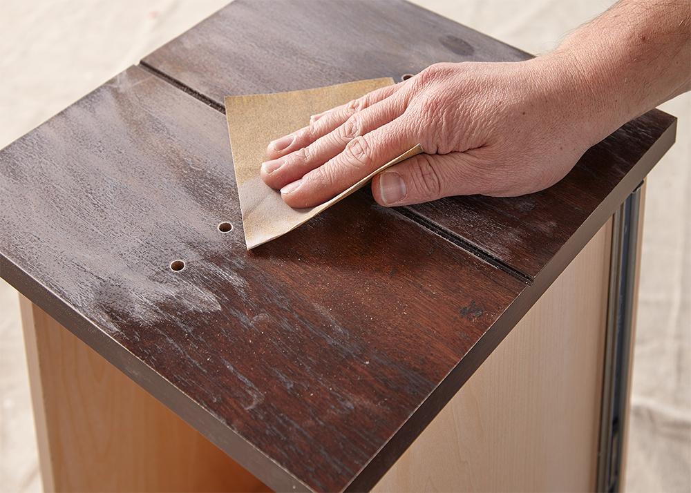 Person sanding a desk drawer