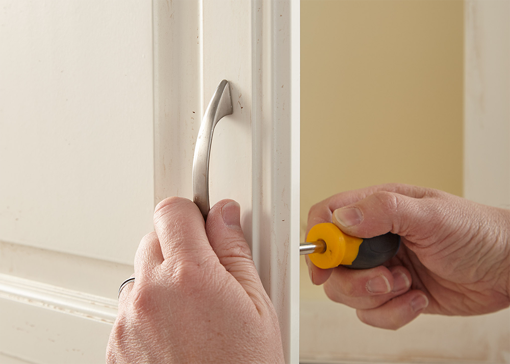 Person removing the handle from a cabinet