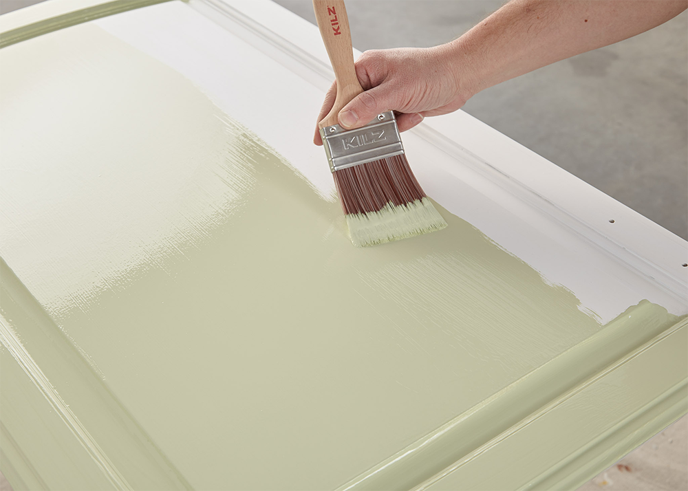 Person painting a cabinet light green