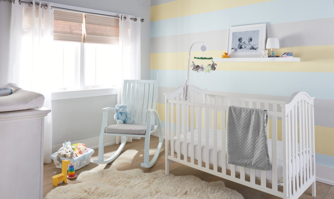 Nursery with blue, yellow, and grey walls and a white crib